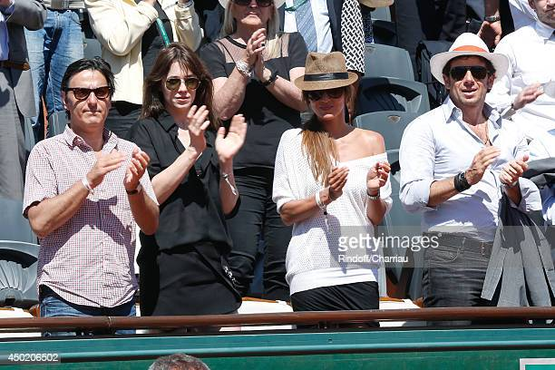 Yvan Attal with Charlotte Gainsbourg and Patrick Bruel with a friend attend the Roland Garros French Tennis Open 2014 Day 13 on June 6 2014 in Paris...