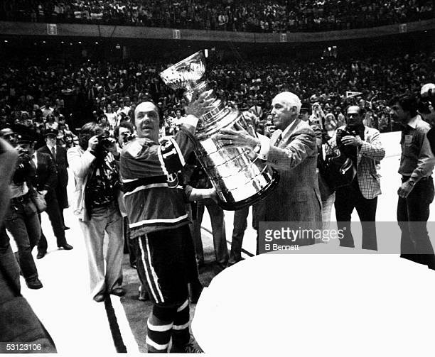 Yvan Cournoyer of the Montreal Canadiens receives the Stanley Cup Trophy from Clarence Campbell after defeating the Philadelphia Flyers in Game 4 of...