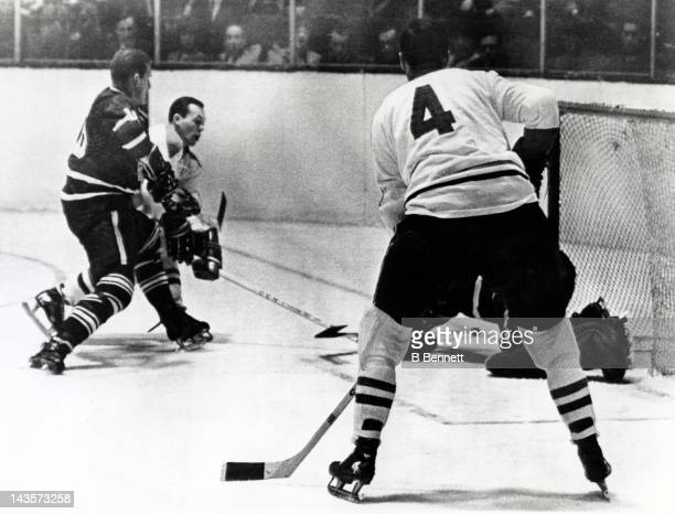 Yvan Cournoyer of the Montreal Canadiens tries to score as he is defended by Larry Hillman of the Toronto Maple Leafs as Jean Beliveau of the...