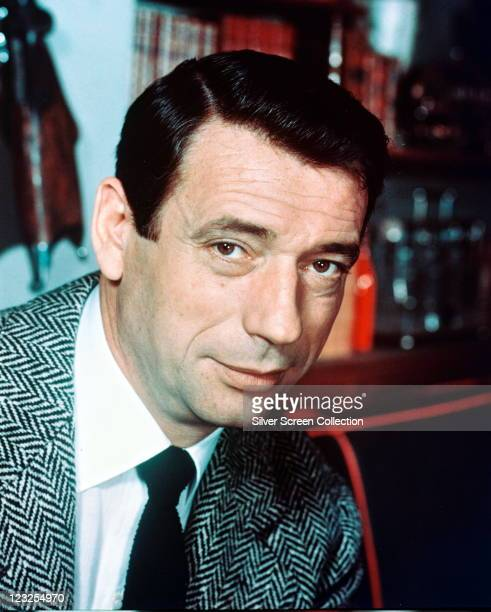 Yves Montand Italianborn French actor and singer wearing a herringbone tweed jacket a white shirt and a black tie circa 1965