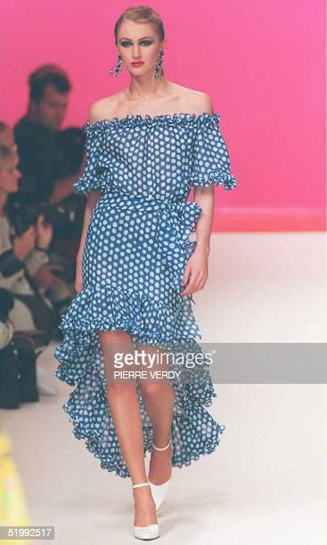 Yves Saint Laurent hikes the ruffled hem above the knees on an offshoulder dress in blue with white polka dots in the SpringSummer 1996 readytowear...