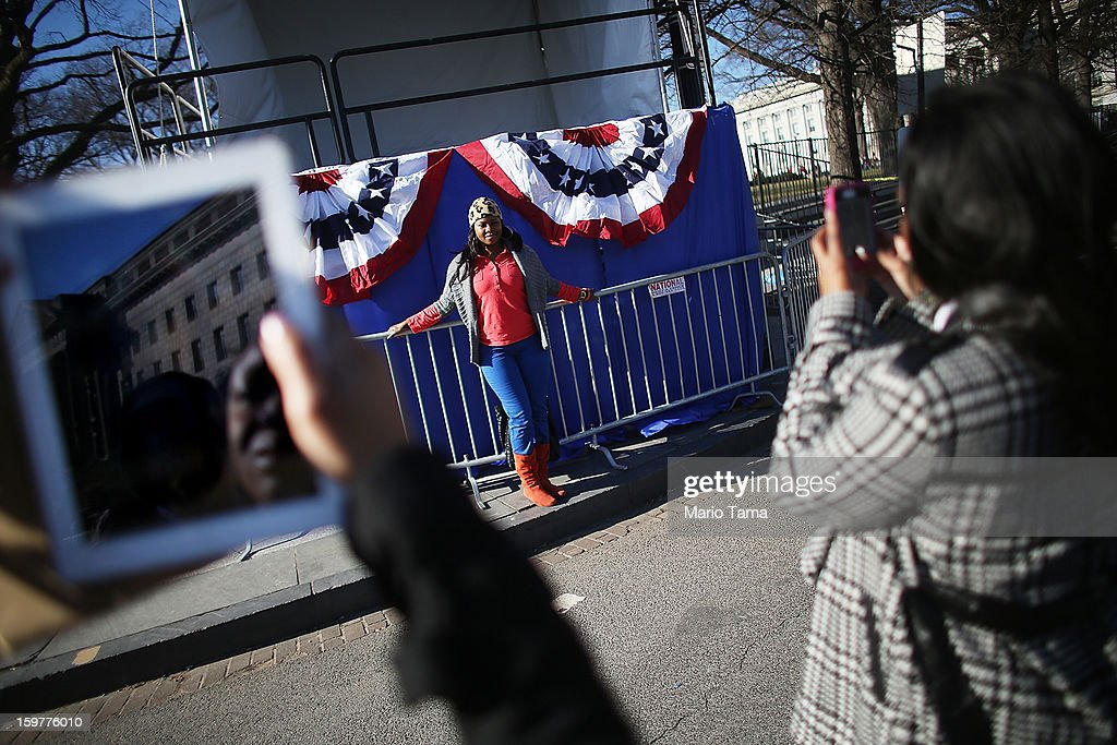 Yvette Adams poses in front of inaugural bunting as Washington prepares for U.S. President Barack Obama's second inauguration on January 20, 2013 in Washington, DC. One day before the public inaugural ceremony at the U.S. Capitol on January 21, Obama was officially sworn in for his second term during a private ceremony surrounded by friends and family in the Blue Room of the White House.