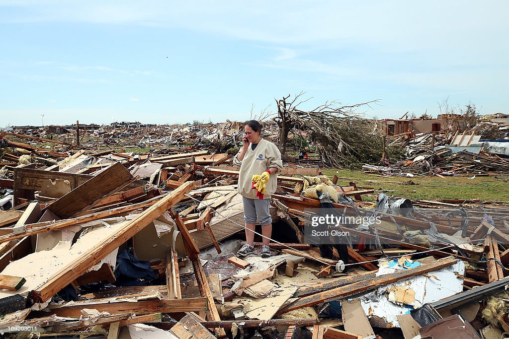 Yvette Martinez (R) stands in the rubble of her house after a tornado destroyed their home on May 21, 2013 in Moore, Oklahoma. The town reported a tornado of at least EF4 strength and two miles wide that touched down yesterday killing at least 24 people and leveling everything in its path. U.S. President Barack Obama promised federal aid to supplement state and local recovery efforts.