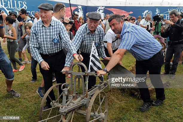 Yvon and Henri two singers of French traditional band from Brittany Les Freres Morvan symbolically use a plow on July 17 2014 on the opening day the...