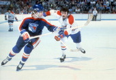 Yvon Lambert of the Montreal Canadiens and Wayne Dillon of the New York Rangers go for the puck during their game circa 1977 at the Montreal Forum in...