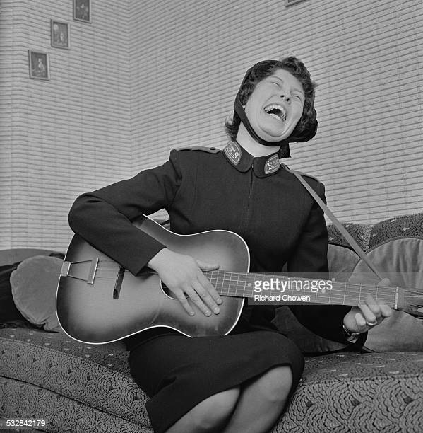 Yvonne Curtis of the Salvation Army practices her guitar playing at her home in Tottenham north London 26th November 1963 The Salvation Army has just...