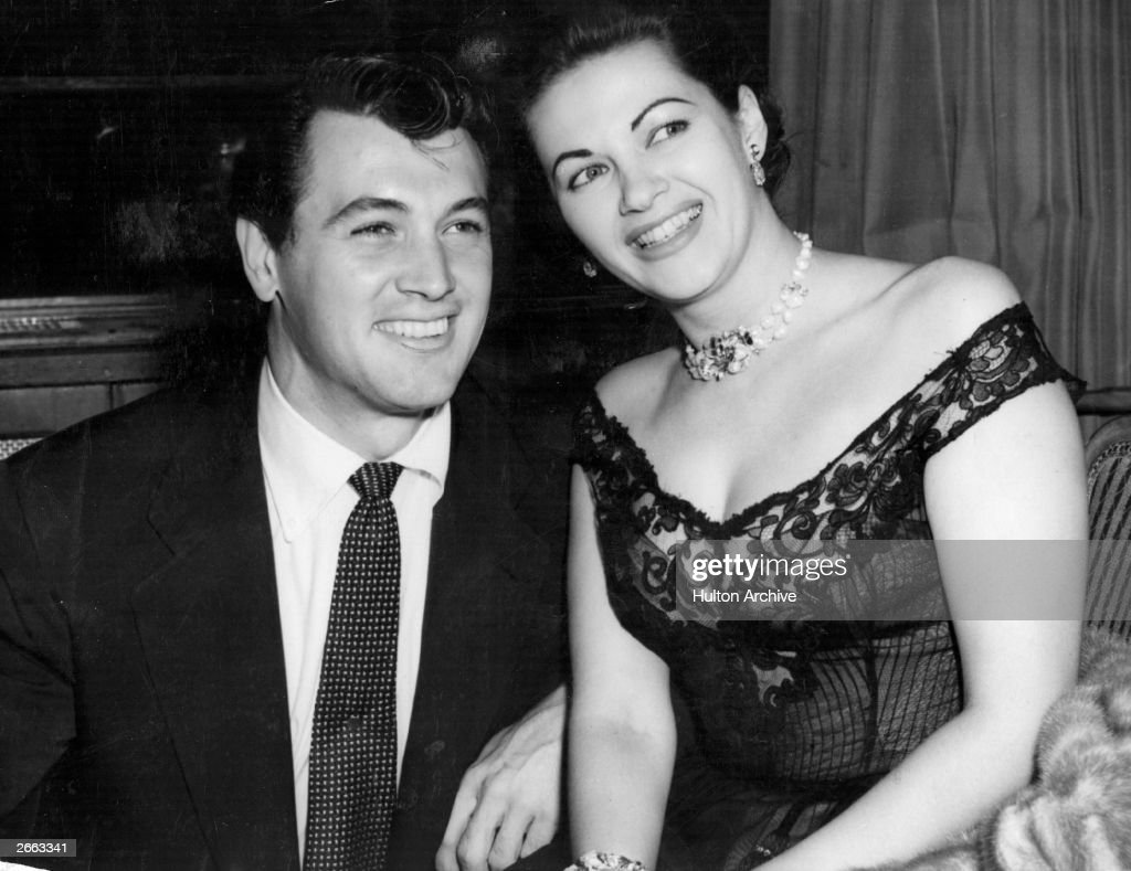 Yvonne De Carlo and fellow actor Rock Hudson smile for the camera during a visit to London.