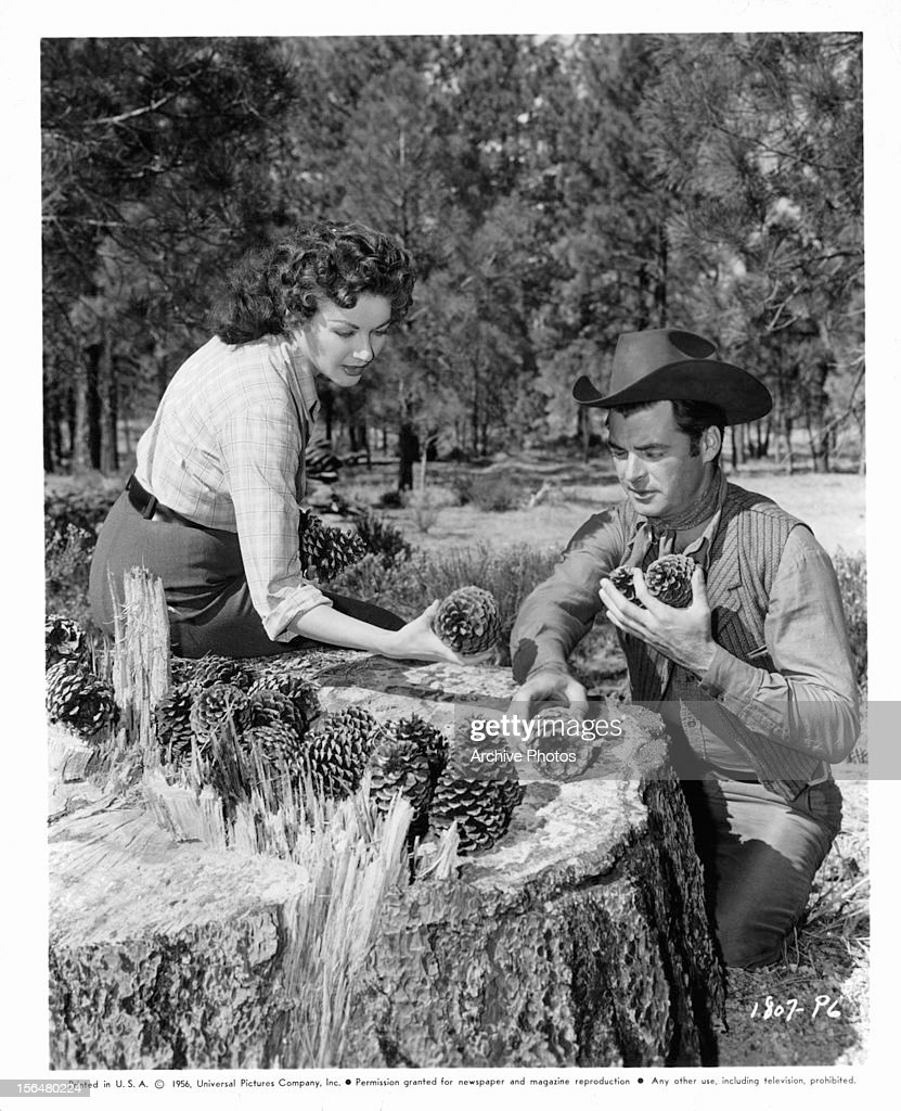 Yvonne De Carlo and Rory Calhoun collecting pine cones in publicity portrait for the film 'Raw Edge' 1956