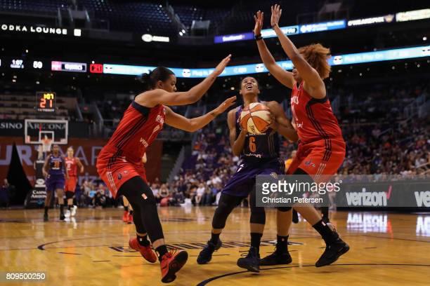 Yvonne Turner of the Phoenix Mercury drives to the basket against Natasha Cloud and Tianna Hawkins of the Washington Mystics during the second half...