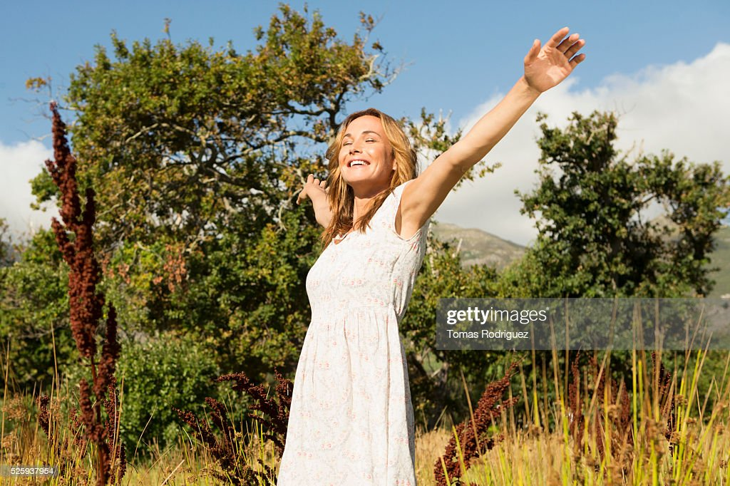 Yyoung woman among field at sunny day : Stock Photo