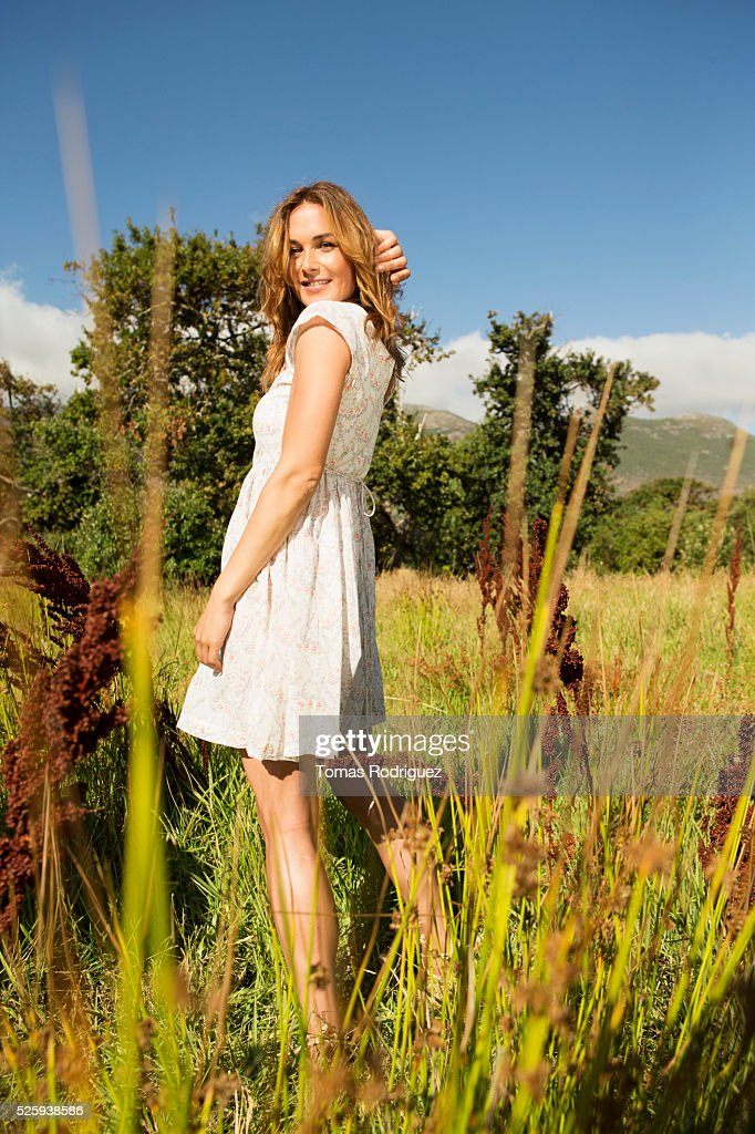 Yyoung woman among field at sunny day : Stock-Foto