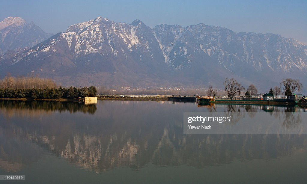 Zabarvan mountains are reflected on the waters of Dal Lake on February 18 2014 in Srinagar the summer capital of Indianadministered Kashmir India...