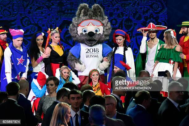 Zabivaka the mascot for the 2018 World Cup poses with performers following the draw for the 2017 FIFA Confederations Cup at the tennis academy center...