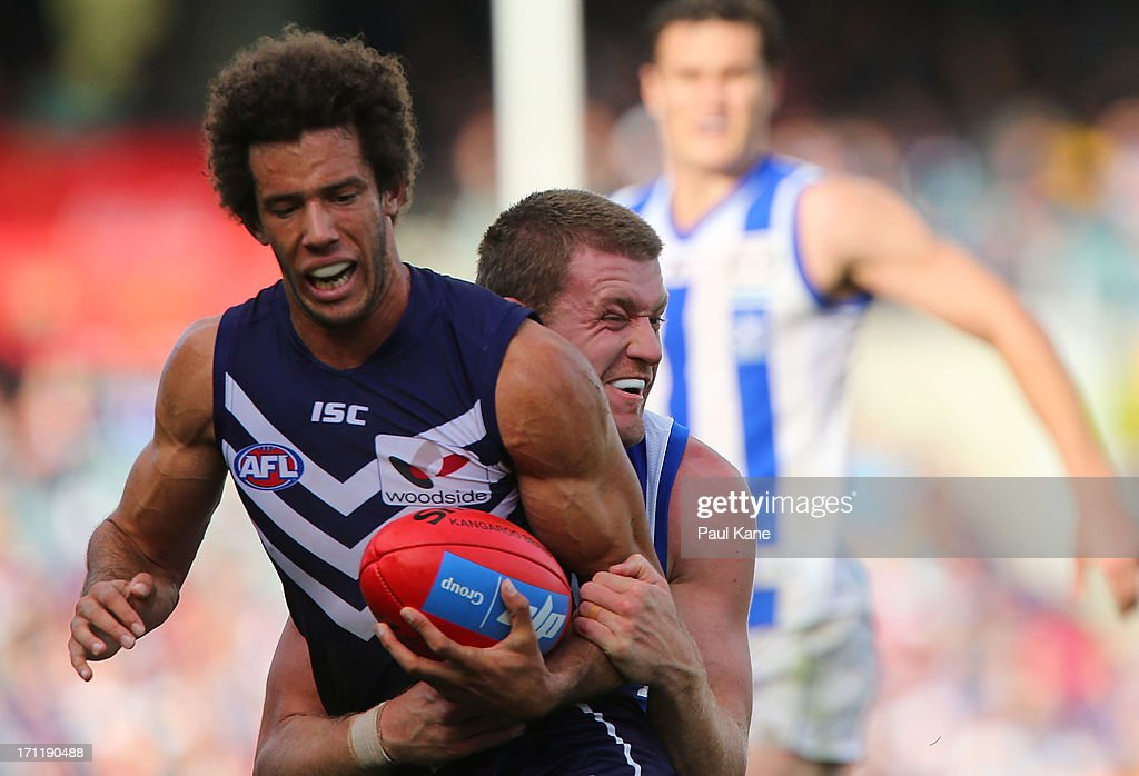 Zac Clarke of the Dockers gets tackled by Lachlan Hansen of the Kangaroos during the round 13 AFL match between the Fremantle Dockers and the North Melbourne Kangaroos at Patersons Stadium on June 23, 2013 in Perth, Australia.