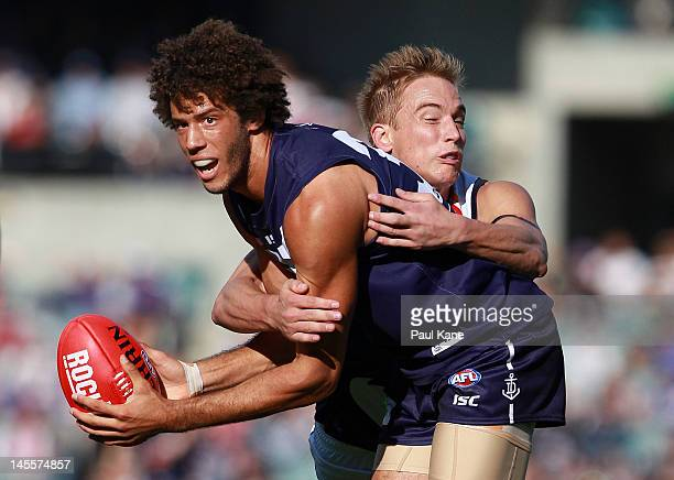 Zac Clarke of the Dockers looks to handball while being tackled by Bernie Vince of the Crows during the round 10 AFL match between the Fremantle...