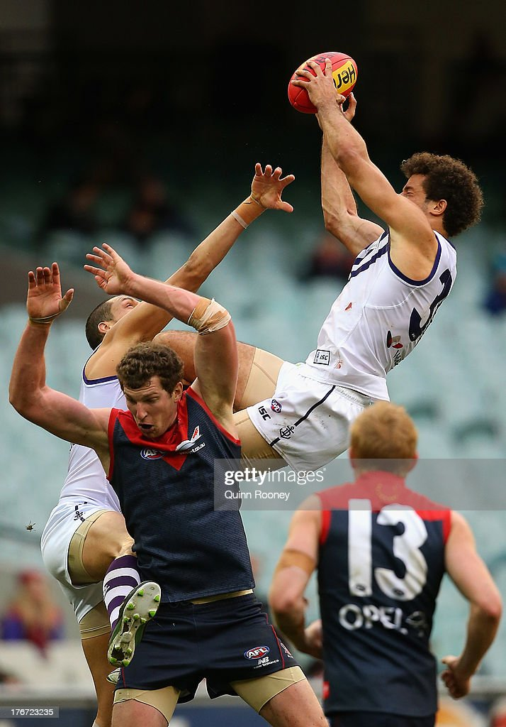 Zac Clarke of the Dockers marks over the top of Jake Spencer of the Demons during the round 21 AFL match between the Melbourne Demons and the Fremantle Dockers at Melbourne Cricket Ground on August 18, 2013 in Melbourne, Australia.