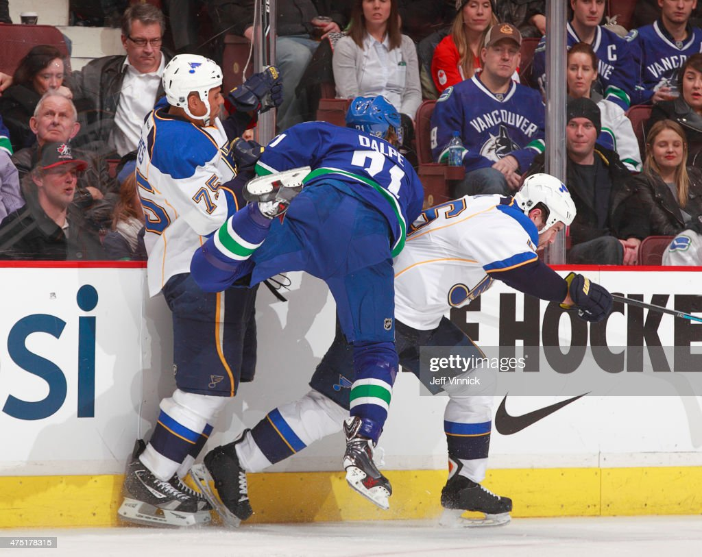 Zac Dalpe of the Vancouver Canucks flies between Ryan Reaves and Roman Polak of the St Louis Blues during their NHL game at Rogers Arena February 26...