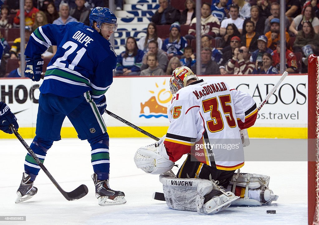 <a gi-track='captionPersonalityLinkClicked' href=/galleries/search?phrase=Zac+Dalpe&family=editorial&specificpeople=5370972 ng-click='$event.stopPropagation()'>Zac Dalpe</a> #21 of the Vancouver Canucks watches teammate Ryan Kesler's (not pictured) shot go past goalie <a gi-track='captionPersonalityLinkClicked' href=/galleries/search?phrase=Joey+MacDonald&family=editorial&specificpeople=2234367 ng-click='$event.stopPropagation()'>Joey MacDonald</a> #35 of the Calgary Flames for a goal during the second period in NHL action on April 13, 2014 at Rogers Arena in Vancouver, British Columbia, Canada.