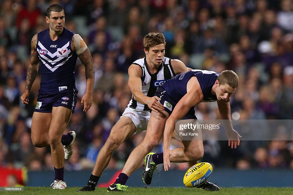 Zac Dawson of the Dockers looks to gather the ball against <a gi-track='captionPersonalityLinkClicked' href=/galleries/search?phrase=Josh+Thomas+-+Australian+Rules+Football+Player&family=editorial&specificpeople=14210396 ng-click='$event.stopPropagation()'>Josh Thomas</a> of the Magpies during the round seven AFL match between the Fremantle Dockers and the Collingwood Magpies at Patersons Stadium on May 11, 2013 in Perth, Australia.