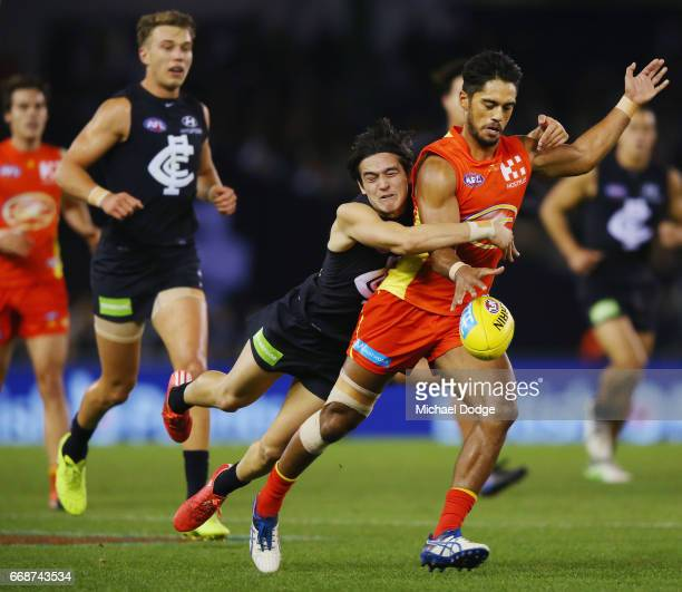 Zac Fisher of the Blues tackles Aaron Hall of the Suns during the round four AFL match between the Carlton Blues and the Gold Coast Suns at Etihad...