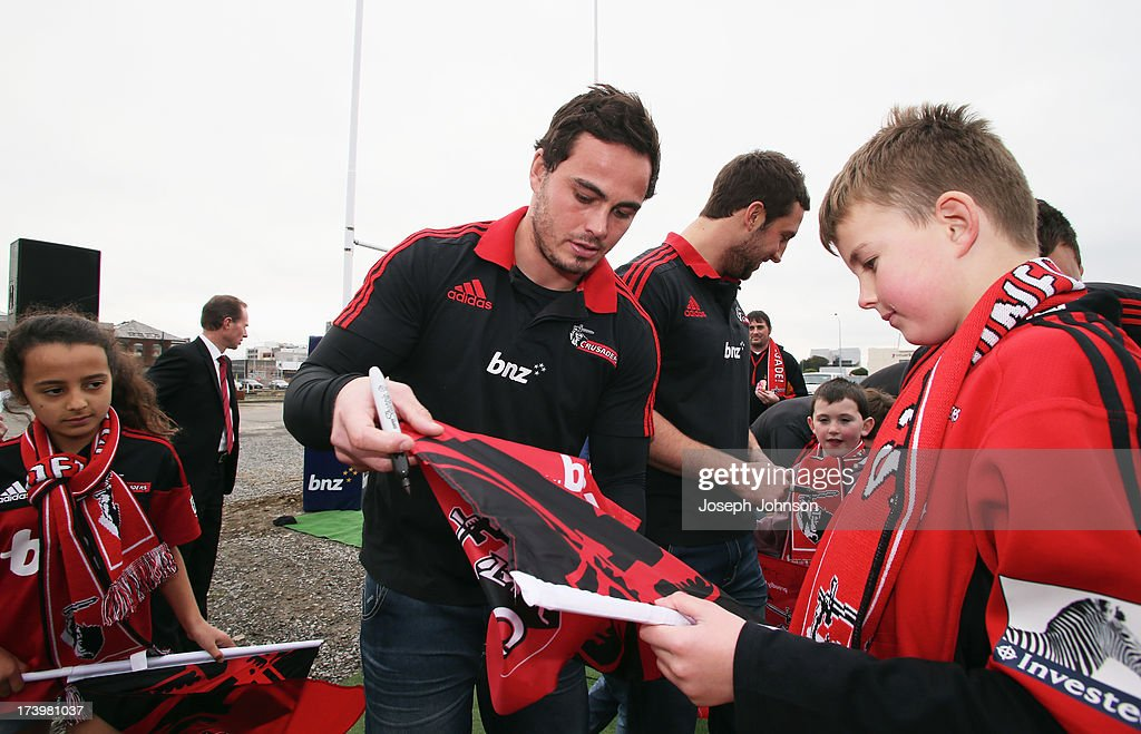 Zac Guildford and Tom Taylor of the Crusaders sign autographs after a media announcement that BNZ will be naming rights sponsor of the Crusaders on July 19, 2013 in Christchurch, New Zealand.