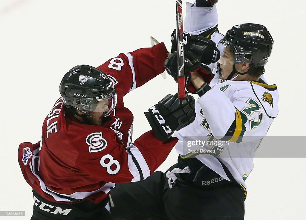 Zac Leslie #8 of the Guelph Storm hits Josh Anderson #77 of the London Knights during the 2014 Memorial Cup tournament at Budweiser Gardens on May 21, 2014 in London, Ontario, Canada.