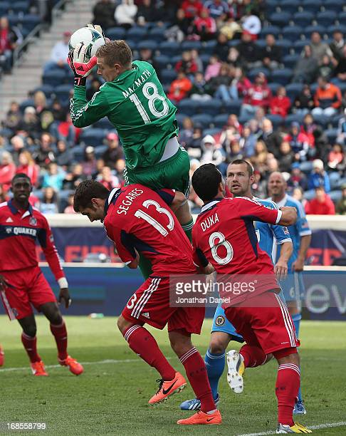 Zac McMath of the Philadelphia Union falls over Gonzalo Segares and Dilly Duka of the Chicago Fire after making a save during an MLS match at Toyota...