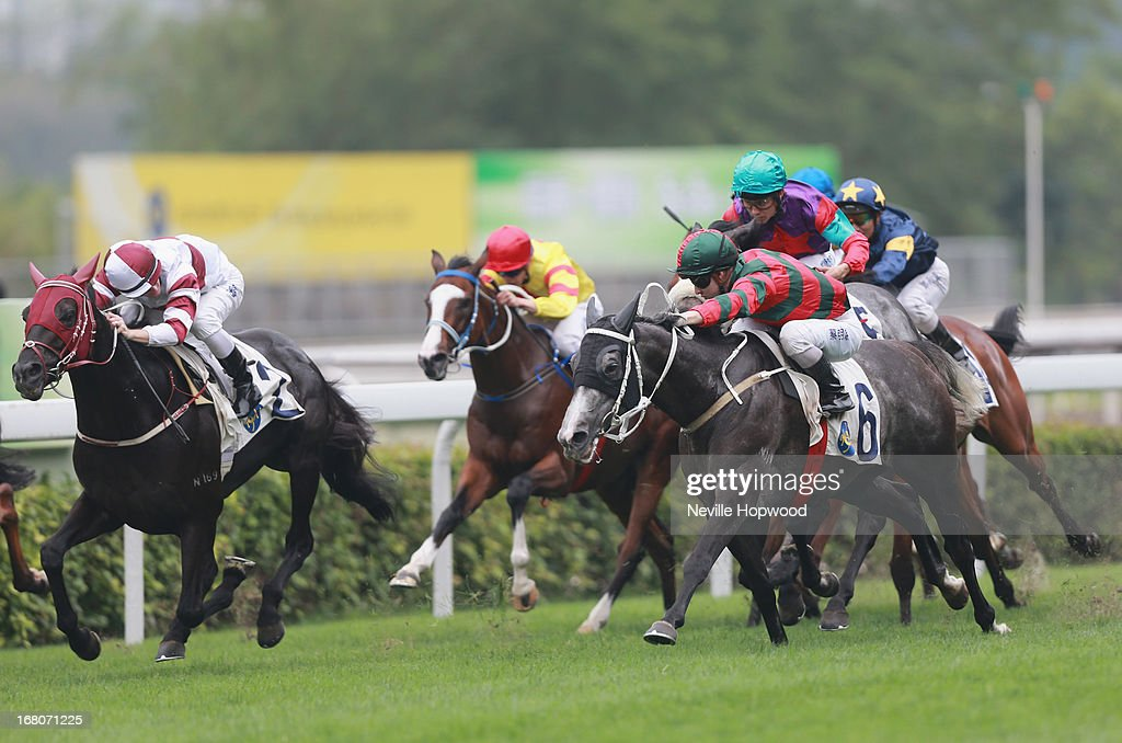 Zac Purton rides Dominant (left) to win from Matthew Chadwick riding Willie Cazals (number 6) to win The Queen Mother Memorial Cup during The Champions Mile meeting at Sha Tin racecourse on May 5, 2013, in Hong Kong, Hong Kong.