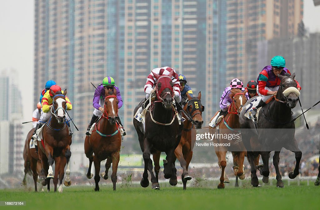 Zac Purton rides Dominant (centre, maroon and white silks) to win The Queen Mother Cup during The Champions Mile meeting at Sha Tin racecourse on May 5, 2013, in Hong Kong, Hong Kong.