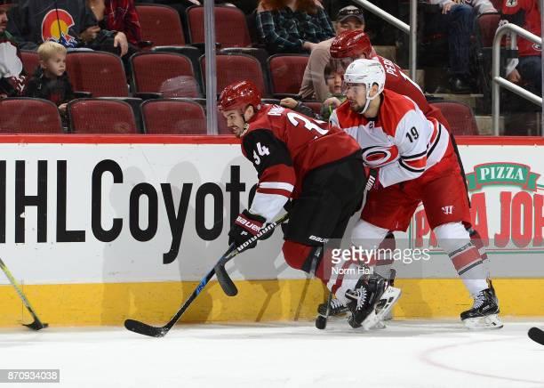 Zac Rinaldo of the Arizona Coyotes battles for a loose puck with Josh Jooris of the Carolina Hurricanes at Gila River Arena on November 4 2017 in...