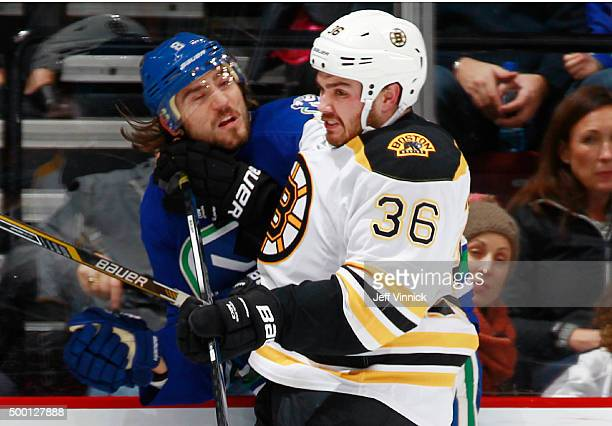 Zac Rinaldo of the Boston Bruins checks Christopher Tanev of the Vancouver Canucks during their NHL game at Rogers Arena December 5 2015 in Vancouver...