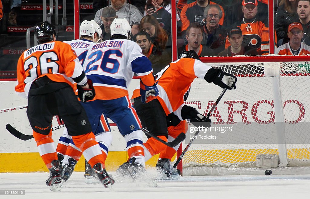 <a gi-track='captionPersonalityLinkClicked' href=/galleries/search?phrase=Zac+Rinaldo&family=editorial&specificpeople=4129574 ng-click='$event.stopPropagation()'>Zac Rinaldo</a> #36 of the Philadelphia Flyers and <a gi-track='captionPersonalityLinkClicked' href=/galleries/search?phrase=Brad+Boyes&family=editorial&specificpeople=275014 ng-click='$event.stopPropagation()'>Brad Boyes</a> #24 and <a gi-track='captionPersonalityLinkClicked' href=/galleries/search?phrase=Matt+Moulson&family=editorial&specificpeople=3365493 ng-click='$event.stopPropagation()'>Matt Moulson</a> #26 of the New York Islanders watch as the puck enters the net off of the skate of Erik Gustafsson #29 of the Flyers n the second period on March 28, 2013 at the Wells Fargo Center in Philadelphia, Pennsylvania. John Tavares (not pictured) of the Islanders was credited with the goal.