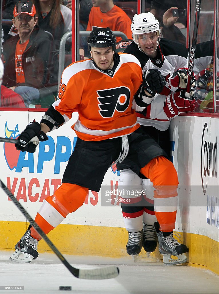 Zac Rinaldo #36 of the Philadelphia Flyers checks Andy Greene #6 of the New Jersey Devils into the boards as they pursue the loose puck on March 15, 2013 at the Wells Fargo Center in Philadelphia, Pennsylvania.