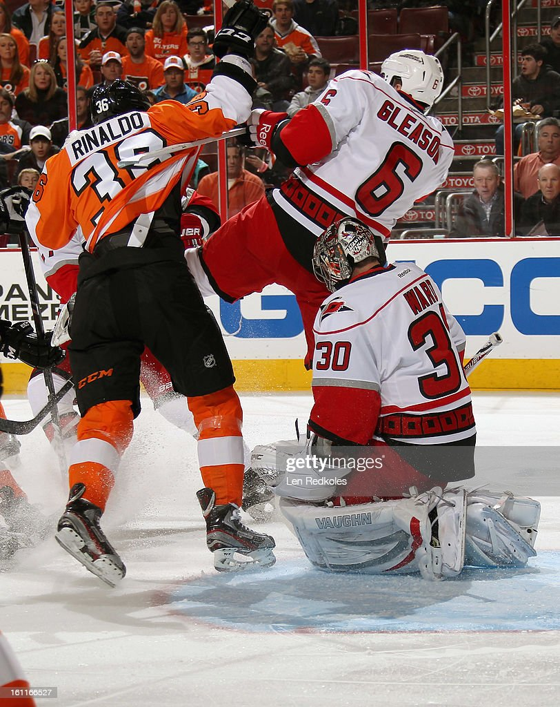 Zac Rinaldo #36 of the Philadelphia Flyers checks Tim Gleason #6 of the Carolina Hurricanes in front of goaltender Cam Ward #30 on February 9, 2013 at the Wells Fargo Center in Philadelphia, Pennsylvania.