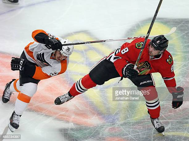 Zac Rinaldo of the Philadelphia Flyers hits Nick Leddy of the Chicago Blackhawks with his stick at the United Center on December 11 2013 in Chicago...