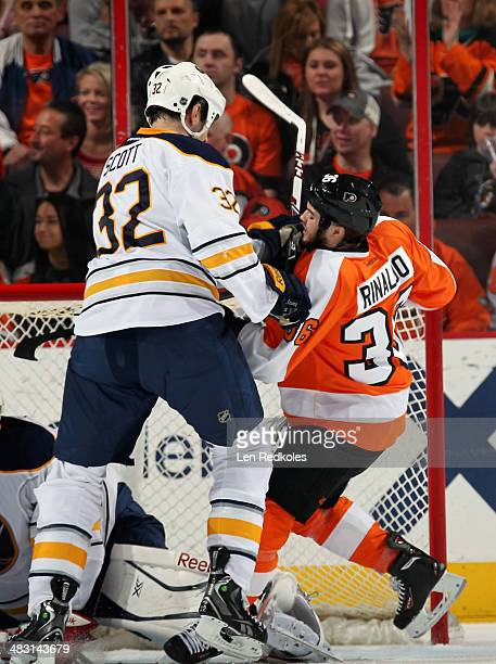 Zac Rinaldo of the Philadelphia Flyers is checked in front of the net by John Scott of the Buffalo Sabres on April 6 2014 at the Wells Fargo Center...