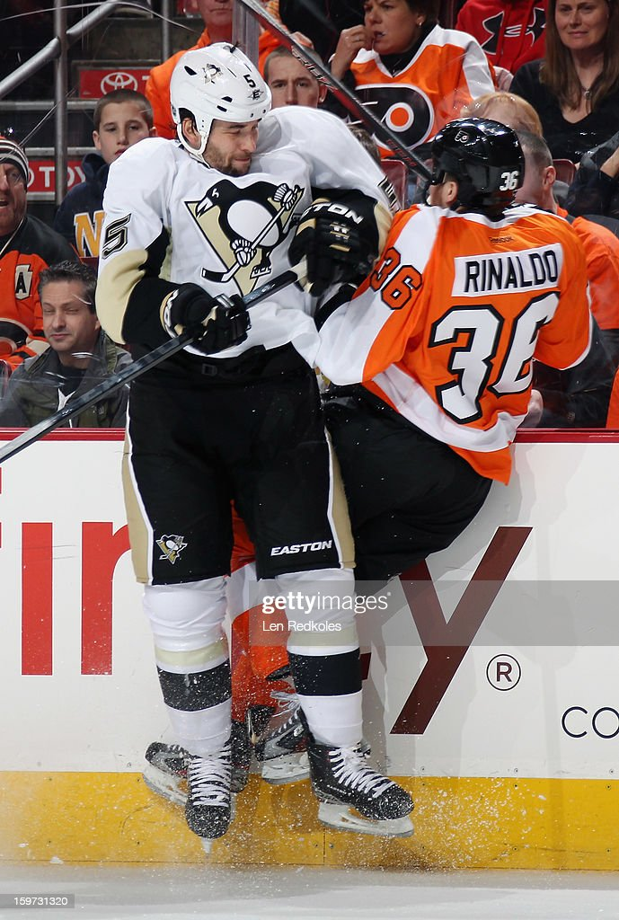 Zac Rinaldo #36 of the Philadelphia Flyers is checked into the boards by Deryk Engelland #5 of the Pittsburgh Penguins on January 19, 2013 at the Wells Fargo Center in Philadelphia, Pennsylvania.