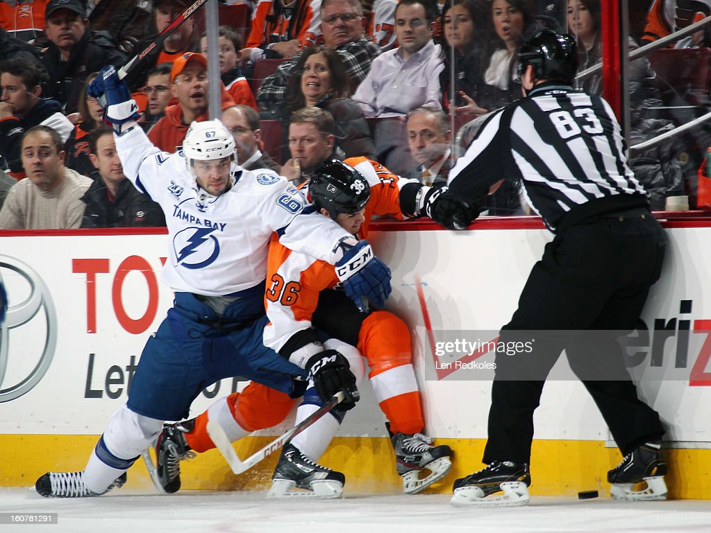 Zac Rinaldo #36 of the Philadelphia Flyers is checked into the boards by Benoit Pouliot #67 of the Tampa Bay Lightning on February 5, 2013 at the Wells Fargo Center in Philadelphia, Pennsylvania.