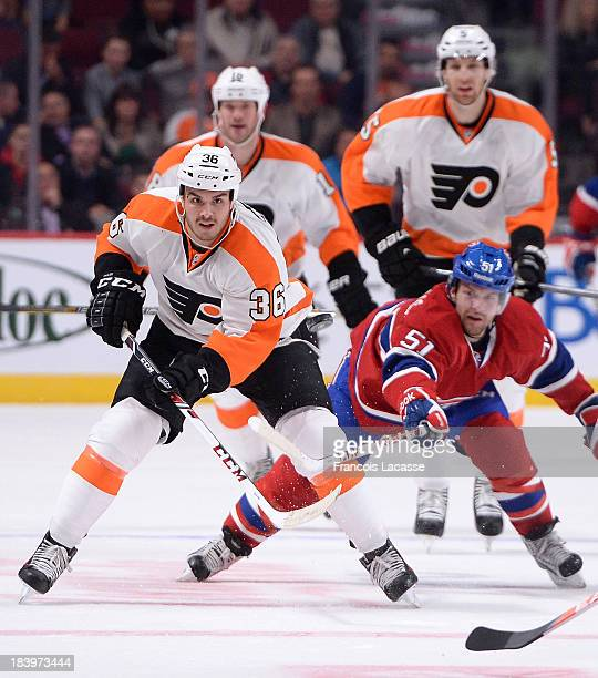 Zac Rinaldo of the Philadelphia Flyers passes the puck against pressure from David Desharnais the Montreal Canadiens during the NHL game on October 5...