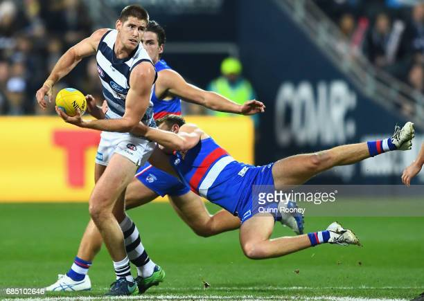 Zac Smith of the Cats handballs whilst being tackled by Jackson Macrae of the Bulldogs during the round nine AFL match between the Geelong Cats and...