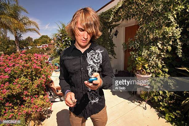 Zac Sunderland checks messages in front of the Sunderland family home in Thousand Oaks as the family waits for more information about his sister Abby...