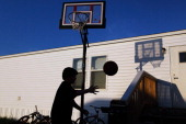 Zach Abrams plays basketball outside his families FEMA trailer that they live in after there home was destroyed when a tornado hit the city one year...