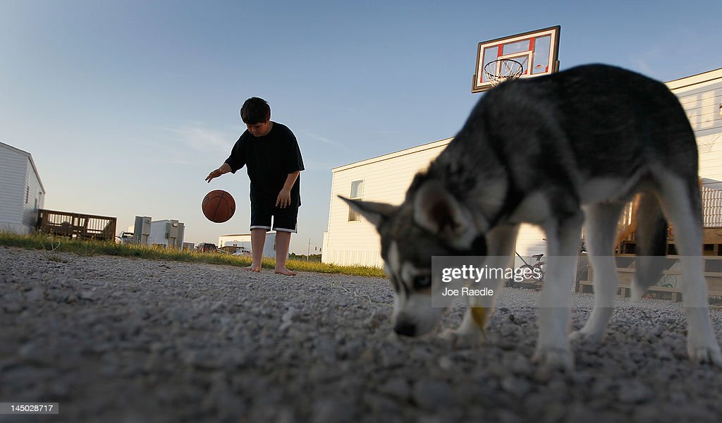 Zach Abrams plays basketball outside his families FEMA trailer that they live in after there home was destroyed when a tornado hit the city one year ago on May 22, 2012 in Joplin, Missouri. Today marked the one-year anniversary of the EF-5 tornado that devastated the town leaving behind a path of destruction along with 161 deaths and hundreds of injuries, but one year later people continue to move out of the temporary FEMA housing sites and into permanent homes.