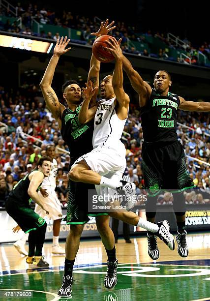 Zach Auguste of the Notre Dame Fighting Irish and teammate Demetrius Jackson try to stop Coron Williams of the Wake Forest Demon Deacons during the...