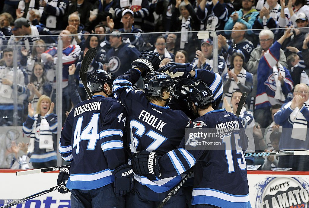 Zach Bogosian #44, Michael Frolik #67 and Matt Halischuk #15 of the Winnipeg Jets celebrate a first period goal against the Chicago Blackhawks at the MTS Centre on November 2, 2013 in Winnipeg, Manitoba, Canada.