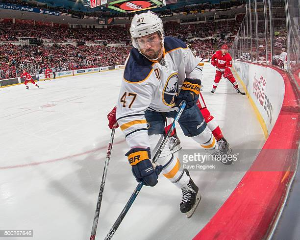 Zach Bogosian of the Buffalo Sabres battles in the corner for the puck during an NHL game against the Detroit Red Wings at Joe Louis Arena on...
