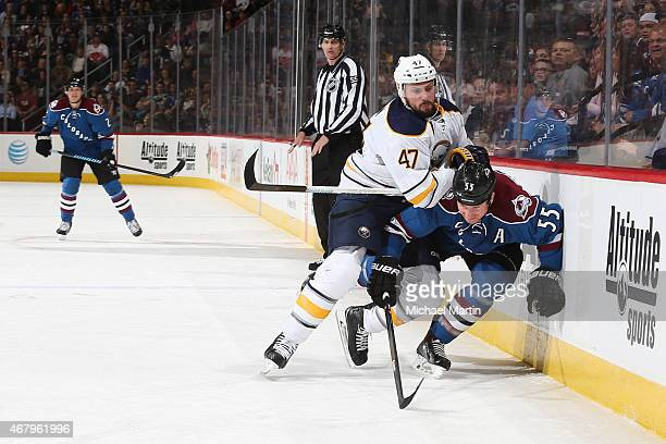 Zach Bogosian of the Buffalo Sabres puts a hit on Cody McLeod of the Colorado Avalanche at the Pepsi Center on March 28 2015 in Denver Colorado