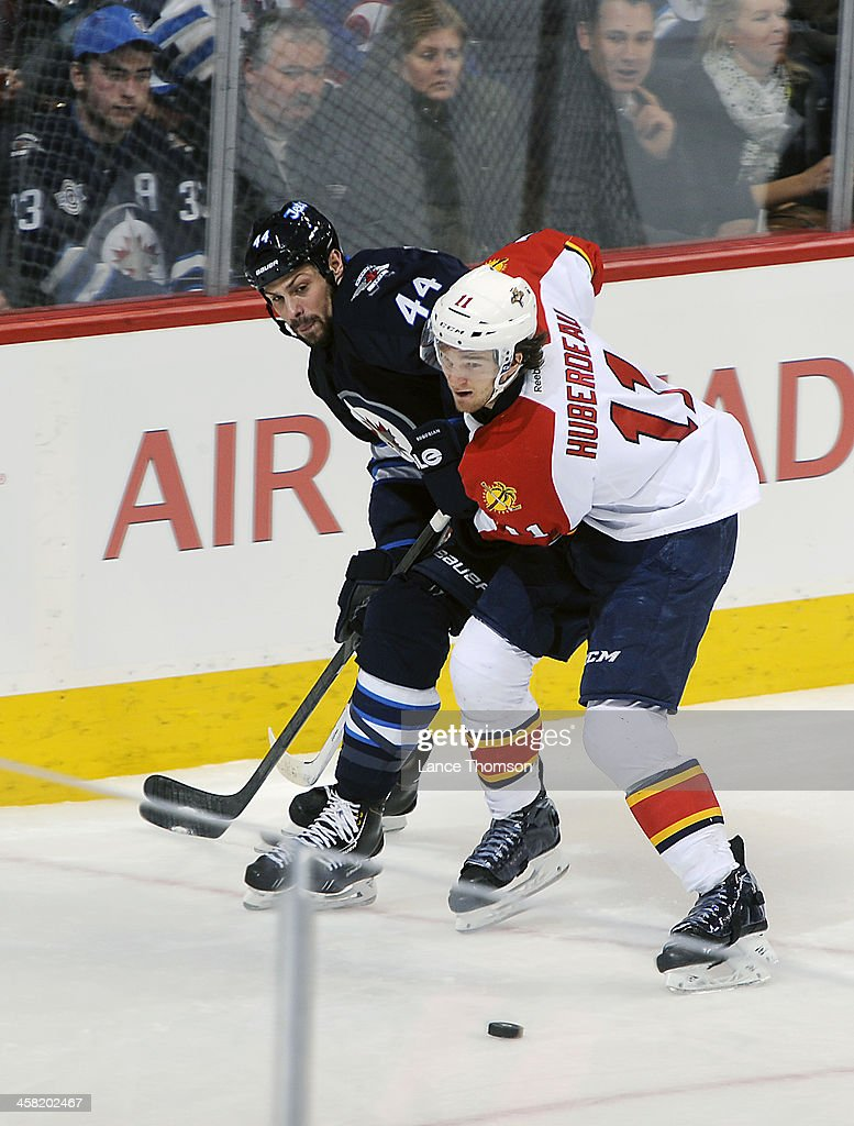 <a gi-track='captionPersonalityLinkClicked' href=/galleries/search?phrase=Zach+Bogosian&family=editorial&specificpeople=4195061 ng-click='$event.stopPropagation()'>Zach Bogosian</a> #44 of the Winnipeg Jets battles <a gi-track='captionPersonalityLinkClicked' href=/galleries/search?phrase=Jonathan+Huberdeau&family=editorial&specificpeople=7144196 ng-click='$event.stopPropagation()'>Jonathan Huberdeau</a> #11 of the Florida Panthers as the puck slides by during second period action at the MTS Centre on December 20, 2013 in Winnipeg, Manitoba, Canada.