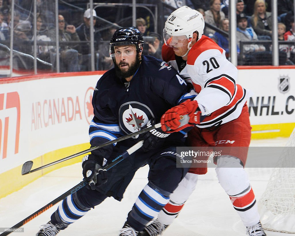 Zach Bogosian of the Winnipeg Jets battles Riley Nash of the Carolina Hurricanes as he plays the puck along the boards during third period action on...