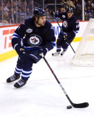 Zach Bogosian of the Winnipeg Jets carries the puck around the net as teammate Nik Antropov follows behind during third period action against the New...
